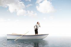 Businesswoman calling for help in boat, open sea. Lonely businesswoman standing in an oar boat in an open sea and crying for help.Concept of travelling Royalty Free Stock Image