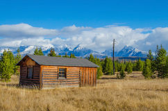 Lonely cabin on the prairie with snowcapped mountain backdrop Royalty Free Stock Photos
