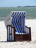 Lonely canopied beach chair 01. Lonely canopied beach chair at coastline Royalty Free Stock Photo