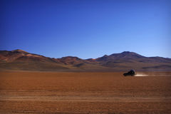 Lonely car in the desert. Lonely car going trough Salvador Dali Desert in Altiplano, Bolivia royalty free stock photography
