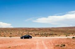 Lonely car on dirt road in desert landscape under blue sky. Lonely car on dirt road in red desert landscape under blue sky stock photos
