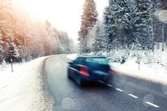 Lonely car driving in winter landscape. Lonely car in motion blur on the road in winter landscape with sunset and glowing light overlays royalty free stock photography