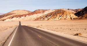 Lonely Car Long Highway Badwater Basin Death Valley. The Mustard Canyon badland area on the right of the two lane higway royalty free stock photo