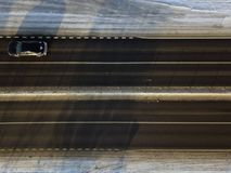 Lonely car on a motorway. Overhead viiew of a lonely car on a motorway, winter scene stock photography