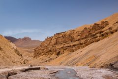 Lonely car riding through curly road in canyon along the river on himalaya highlands. Scenic landscape with weird form mountains. Region Ladakh. India. State stock photo