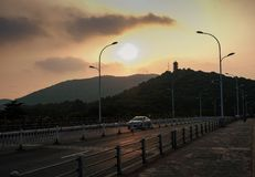 A Lonely Car During the Sunset in the streets of Wuxi. A car crossing the bridge under a setting sun in the City of Wuxi, China stock images
