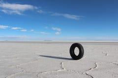 Lonely car tire in the salt lakes of Bolivia. Lonely car tire standing on the salt lakes of Bolivia, salar de Uyuni royalty free stock photo