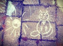 Lonely cat and the sun. Drawing on the bricks royalty free stock image
