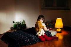 Lonely caucasian girlie in the empty room holding a doll. Lonely caucasian girlie in the empty dark room holding a doll, bottles in background royalty free stock image