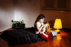 Lonely caucasian girlie in the empty room holding a doll. Lonely caucasian girlie in the empty dark room holding a doll, bottles in background stock image