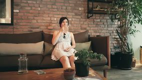 Lonely Caucasian woman in dress waiting her date in a cafe. Beautiful young brunette lady drinking water while waiting her friend in a cafe stock footage