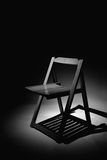 Lonely Chair. Empty wooden chair under a spotlight Stock Photos