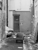 Lonely chair in an alleyway. Representing homelessness, loneliness etc Stock Image