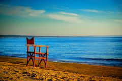 Lonely chair on the beach. At the end of the summer royalty free stock photography