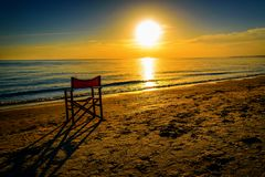 Lonely chair on the beach at sunset. Lonely chair on the beach at beautiful orange sunset royalty free stock images