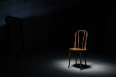 Lonely chair at the empty room. Lonely chair in the spot of light on black background at empty room Stock Images