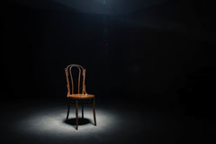 Lonely chair at the empty room. Lonely chair in the spot of light on black background at empty room Royalty Free Stock Photos