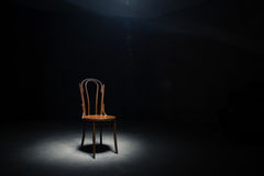 Lonely chair at the empty room. Lonely chair in the spot of light on black background at empty room Stock Photo