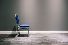 A lonely chair with silver legs in blue. It stands at the gray wall. At the bottom of a wide white baseboard and laminate. The stock photos