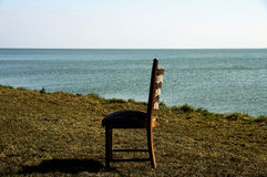 Lonely chair at water. A scene with a single chair at the water with shade and sun Royalty Free Stock Photography