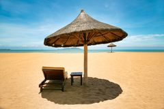 Lonely chaise longue and table, standing on a deserted beach under umbrellas of palm leaves. Sanya, Hainan royalty free stock images
