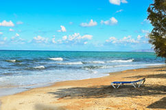 Lonely chaise lounge on the beach. Standing in the shade of the tree. view of the beautiful sea and cloudy blue sky Royalty Free Stock Images