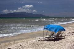 Two sun beds on an empty beach/. Lonely chaise lounges on an ocean coast Royalty Free Stock Photos