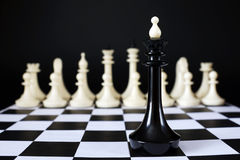 Lonely chess king in front of enemy team. Unequal battle Royalty Free Stock Image