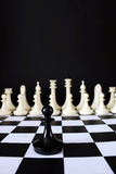 Lonely chess pawn in front of enemy team. Courage and boldness Royalty Free Stock Photo