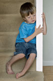 Lonely child. Concept of Child Abuse: Lonely boy sits on the stairs Stock Image