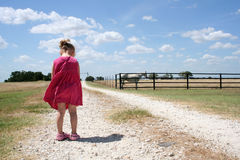 Lonely Child. A little girl in a pink dress stands alone on a dirt road in the country Royalty Free Stock Photo