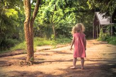 Lonely child girl barefoot standing alone on rural countryside road among trees in park and looking into the distance concept chil royalty free stock photo