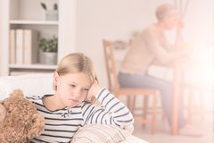 Lonely child and ill mother. Lonely child sitting on sofa, ill cancer mother in background Royalty Free Stock Photo