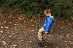 Free Lonely Child In A Blue Jacket Sits On A Swing In A Park In An Autumn Park, The Concept Of Loneliness Royalty Free Stock Images - 160846489