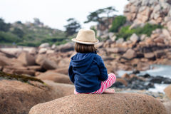 Lonely child sitting on backside for boredom, freedom or sadness. Lonely young child with a summer hat sitting on a granite stone on the backside looking away to Stock Images