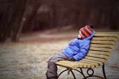 Lonely child sitting on bench in winter park. Lonely child sitting on bench in park, winter depression Royalty Free Stock Photography