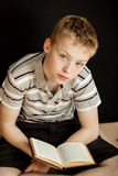 Lonely child sitting and reading a book. Lonely child with calm expression sitting cross legged and reading a small hard cover book Royalty Free Stock Photography