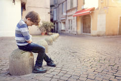 Lonely child sitting on a street corner. Upset problem child sitting on a street corner concept for bullying, depression, child protection or loneliness royalty free stock photography