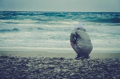 Lonely child in stormy weather in the beach stock photos