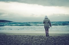 Lonely child in stormy weather in the beach royalty free stock photos