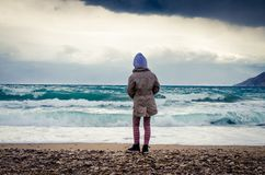 Lonely child in stormy weather in the beach stock photo