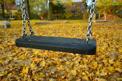 Lonely child swing. On a children playground in autumn Royalty Free Stock Image