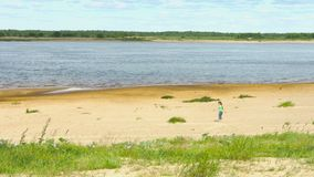 Lonely child walking along the shore of a large river Stock Photo
