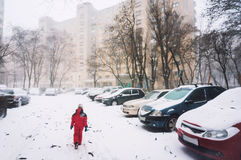 Lonely child walking in snow. On an empty city street Royalty Free Stock Photos