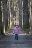 Lonely child walks along an alley. Lonely girl is walking through an alley Royalty Free Stock Photography