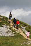 Lonely child walks on the mountain path next to the huge wall of Royalty Free Stock Images