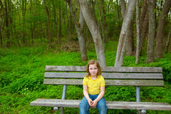 Lonely children girl happy sitting on park bench Stock Images