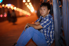 Lonely chinese young man. In the street at night Stock Images