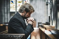 Lonely Christian man praying in the church stock images