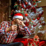 Lonely Christmas nerd with a laptop under the tree royalty free stock photo